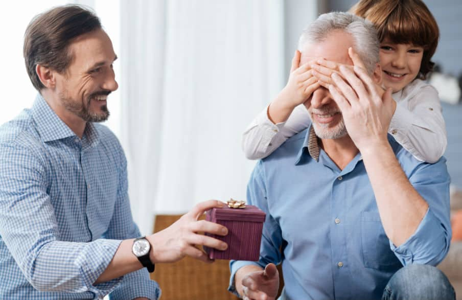 Ældre far der modtager gave fra sin voksne søn, men barnebarnet holder bedstefar for øjnene