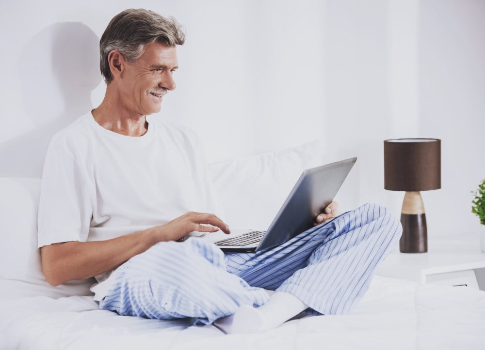 Mand der sidder i sin seng